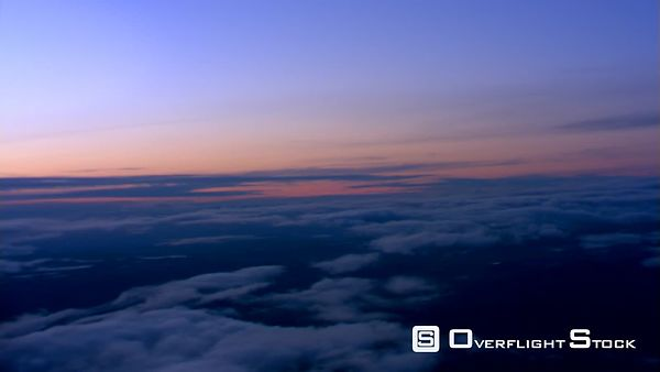 Sunset flight over broken cloud layer over rugged terrain, passenger POV