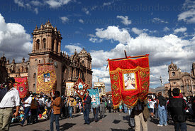Devotees carrying banners in front of cathedral during parades forat Corpus Christi festival , Cusco , Peru
