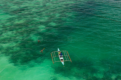 Aerial view of farmers on outrigger boat working at a seaweed farm growing agar-agar for processing into carageenan (gelatino...