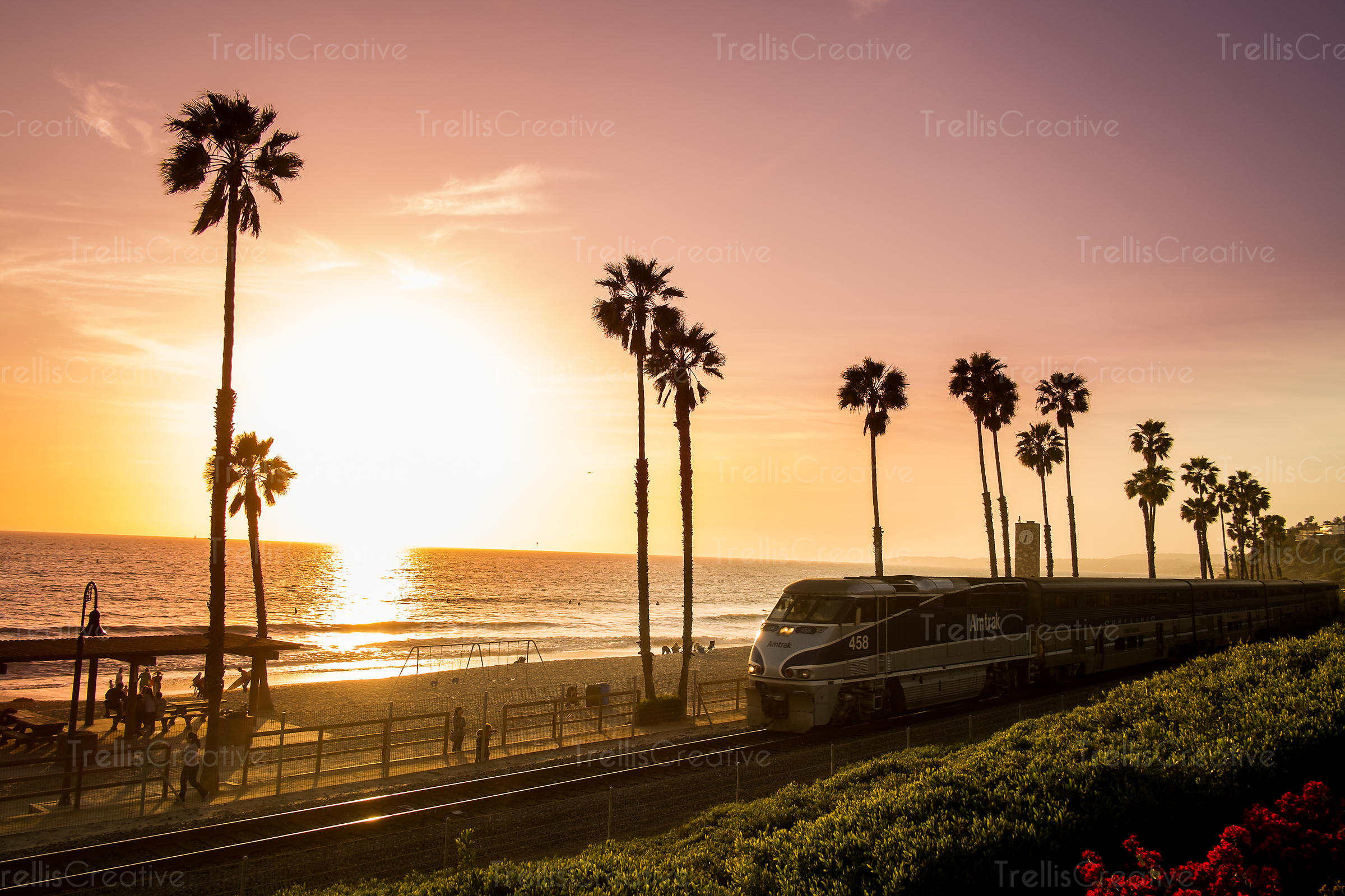 Amtrak train travels along the beach in San Clemente, California during a colorful sunset
