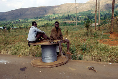 Burundi - Ruyigi - Men sitting on a drum of wire