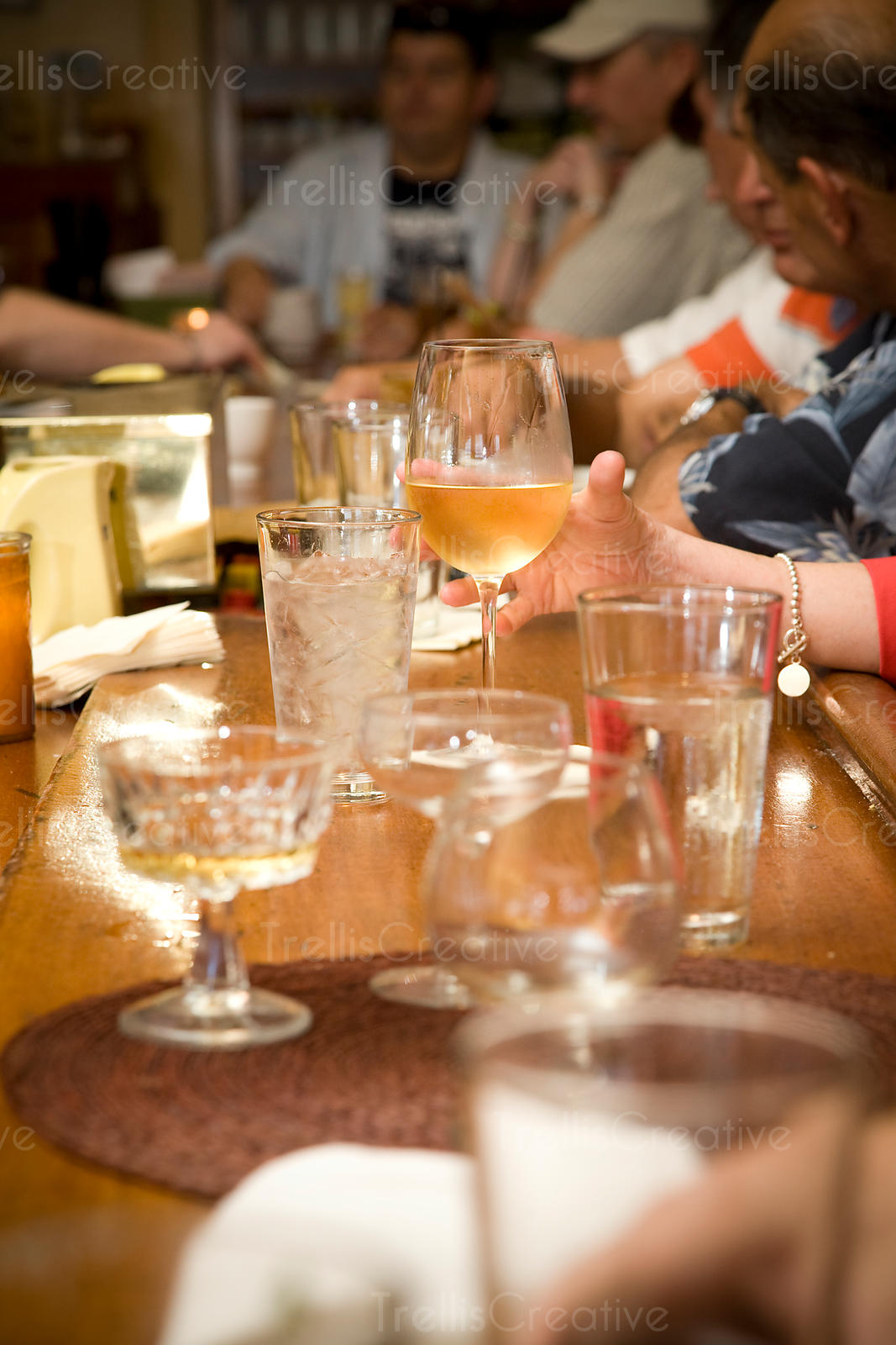 A woman's hand reaches for a glass of white wine on the bar