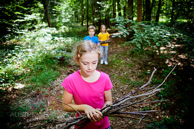 Children picking up firewood in forest, Munich, Bavaria, Germany