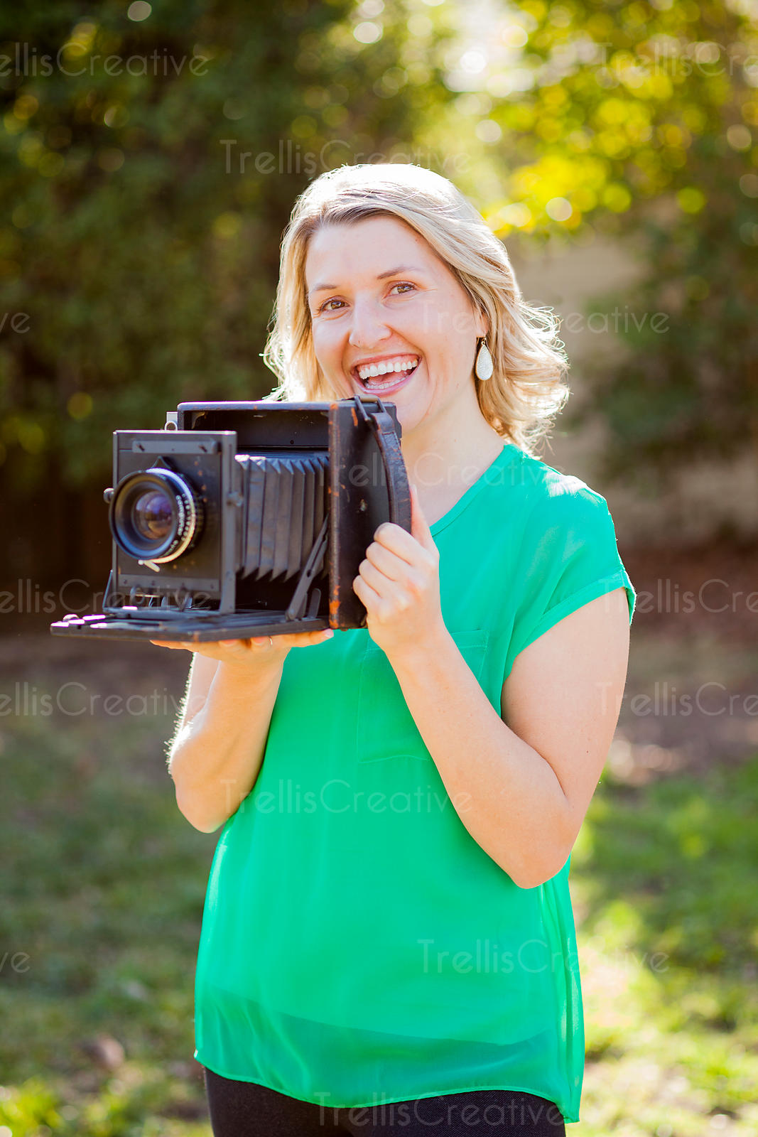 Pretty blonde woman holding an old camera