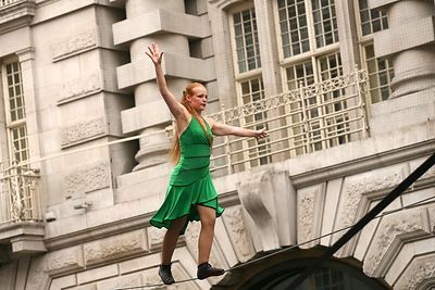 Woman in green dress walks a tightrope in Regent Street, London