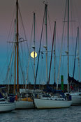 Moon rising behind moored yachts