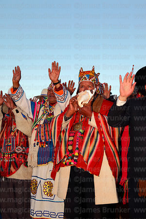Aymara shamans or amautas hold up their hands to receive the sun's energy at sunrise during Aymara New Year celebrations, Tiw...