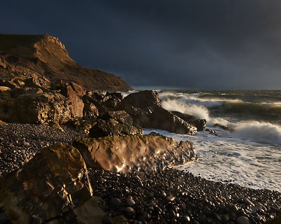 Waves break on the beach at Pier bottom with sunlight on St Aldhelm's Head with a dark rain laden sky as a backdrop.
