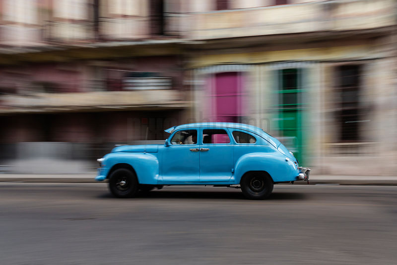 A Vintage American Car Speeding Past Colorful Doors in Central Havana