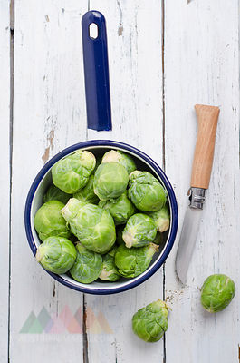 Saucepan of raw Brussels sprouts on wood