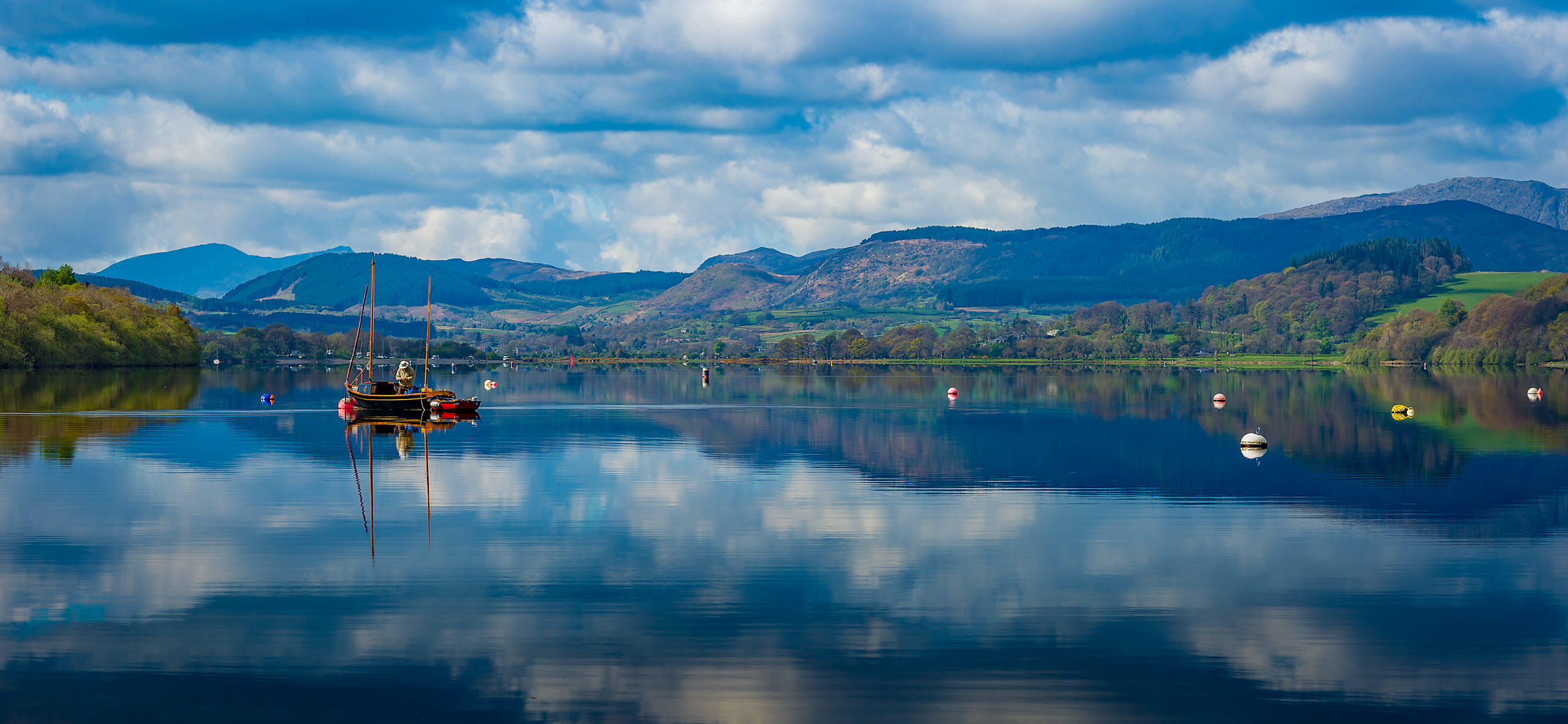 Fisherman in Boat on Calm Lake with Reflection in the Water