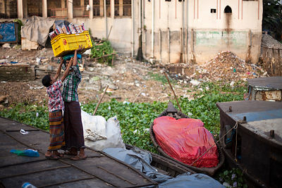 Bangladesh - Dhaka - A boy helps his friend to balance a crate of bread on his head at the Sadarghat ferry terminal
