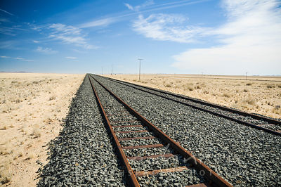 A flat straight section of railway in the desert disapearing into the distance, with a few telephone poles running next to it.