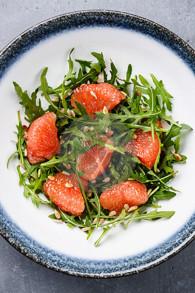Arugula salad with Grapefruit and sunflower seeds on gray concrete background close-up