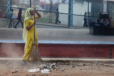 A woman sweeps and cleans trash at a train station in Delhi, India