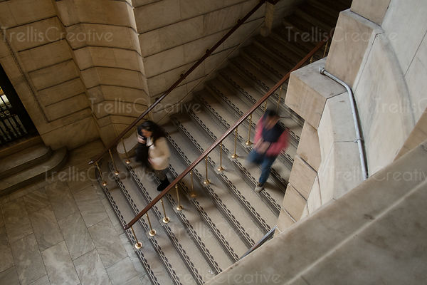 People walking up and down marble steps