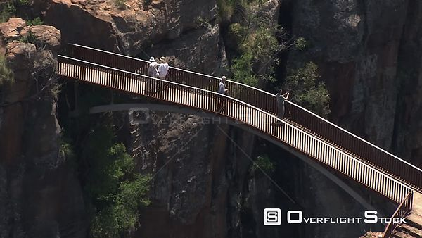 Aerial shot of people standing on a bridge admiring the Bourke's Luck potholes North West South Africa