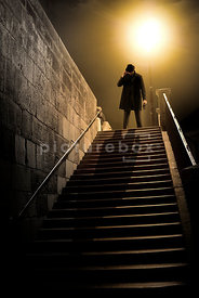 An atmospheric image of a mystery man standing at the top of some steps at Night.