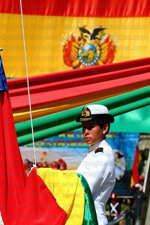 Female navy cadet holding Bolivian flag before flag raising ceremony at start of official events for Dia del Mar / Day of the...