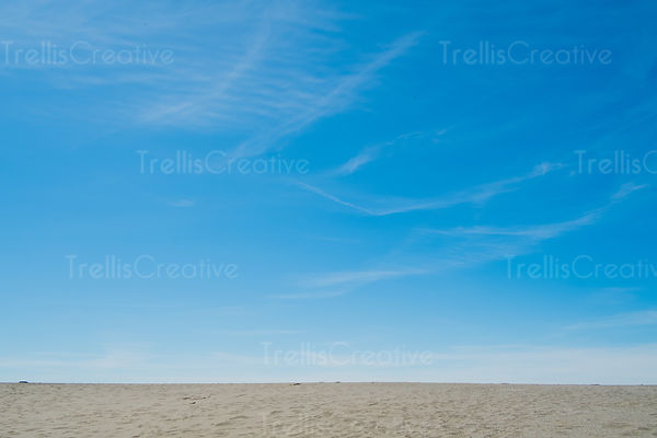 Sandy beach against blue sky with whispy clouds