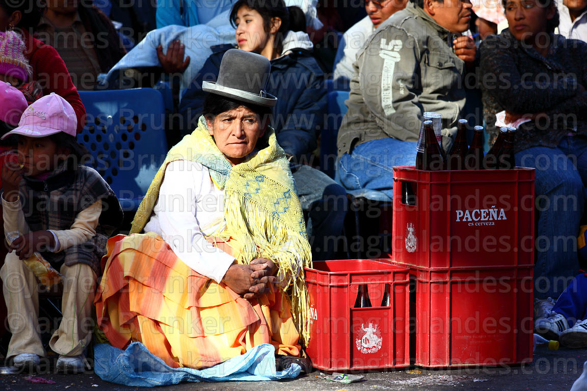 Aymara woman in crowd selling beer during the Gran Poder festival, La Paz, Bolivia