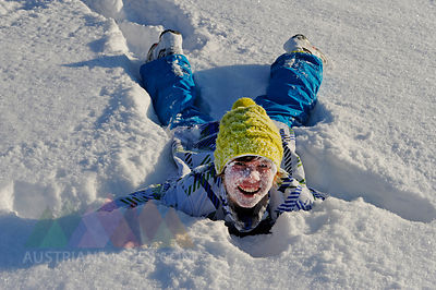 Germany, Bavaria, Boy lying down in snow, smiling