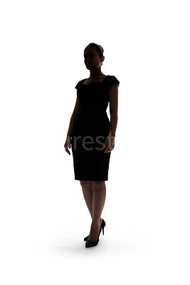 A woman in a black dress, standing, in silhouette – shot from low level.