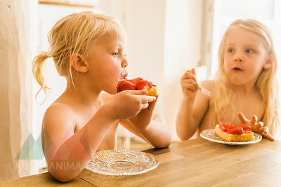 Two blond girls eating strawberry cake