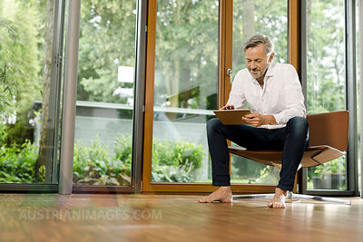Barefoot man sitting on chair in his living room using tablet