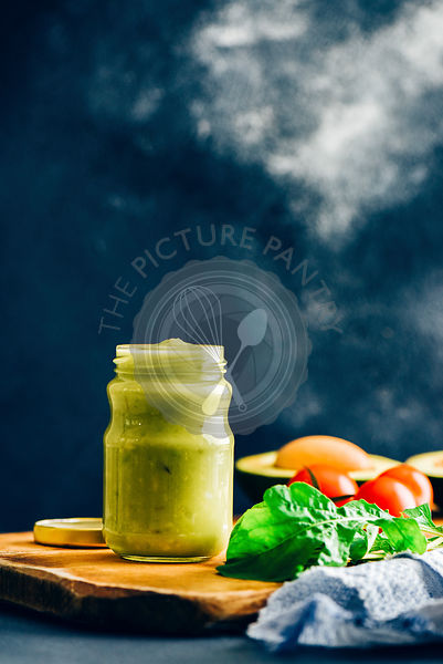 Avocado dressing in a glass jar photographed on a wooden board from front view. Arugula leaves, tomatoes, avocado with its pi...