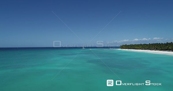 Caribbean beach with palm trees. Faster flight forward over the sea and catamaran . Saona Island, Dominican Republic