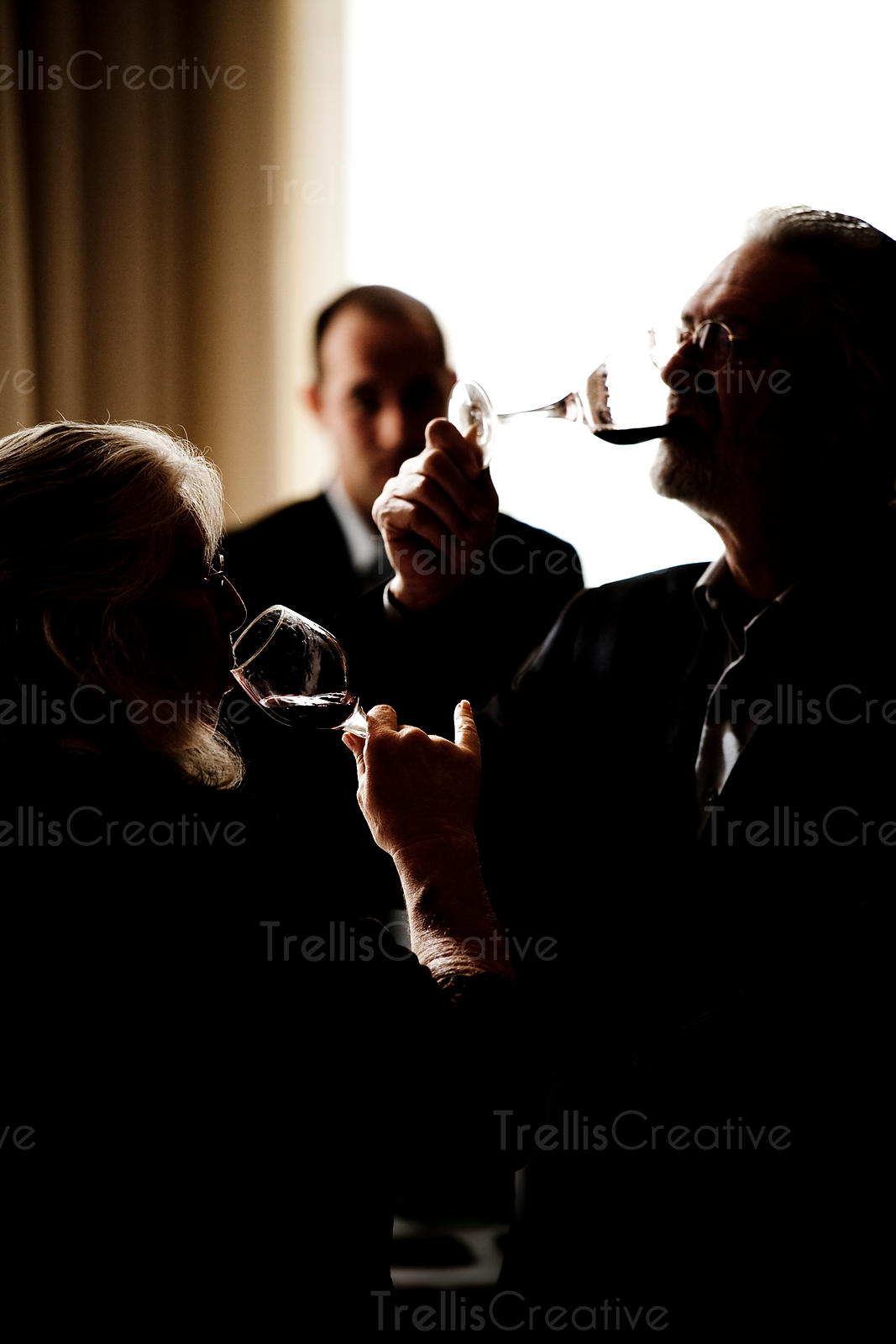 Silhouette of an older man and woman tasting wine