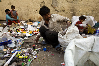 India - New Delhi - Buddhi-Lala and Roshan sort rubbish into piles to sell on the pavement where they live