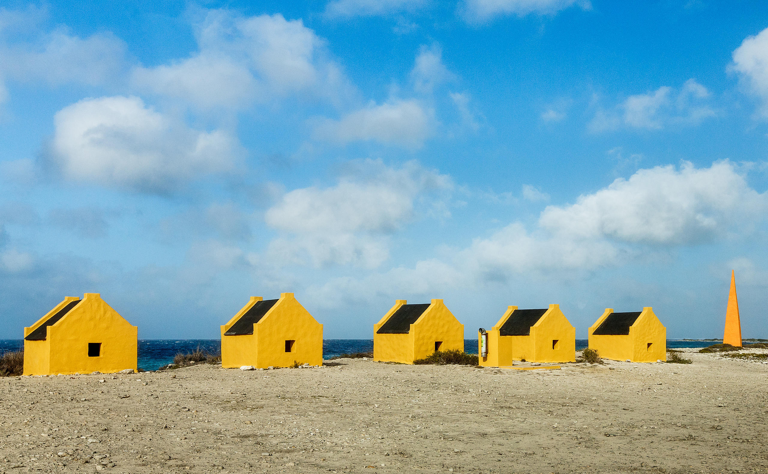 Yellow slave huts against blue sky in Bonaire