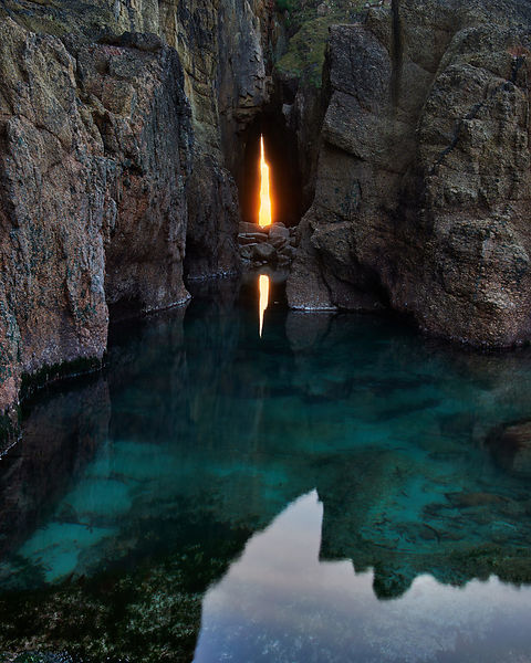 The winter sun sets through the Zawn Pyg (Song of the Sea) rock arch at Nanjizal (Mill Bay) near Land's End in the far West o...