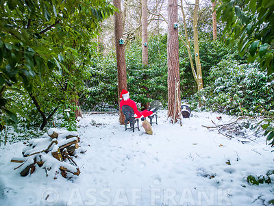 Santa Claus with gift sack sitting on chair in forest covered with snow