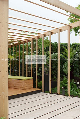 Terrasse contemporaine, pergola en bois. Dalles 'Romaine Antique' (HMT). Paysagiste : Didier Danet. Suresnes (92), France