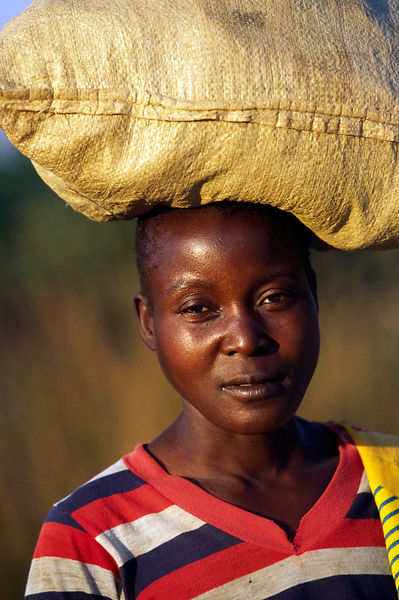 Burundi - Ruyigi - A woman returning from market with a sack of grain balanced on her head