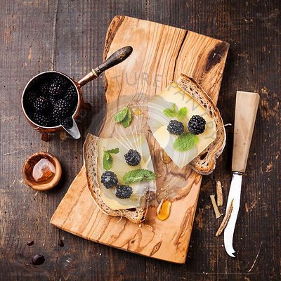 Italian bruschetta sandwich with cheese and blackberry on fresh bread on dark wooden background