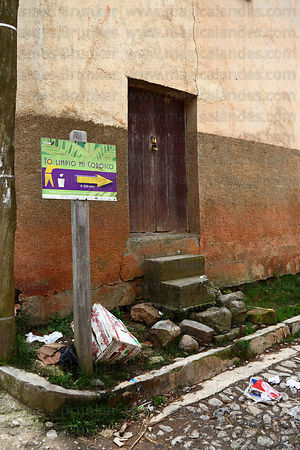 Rubbish dumped next to sign ordering people not to drop litter , Coroico , Bolivia