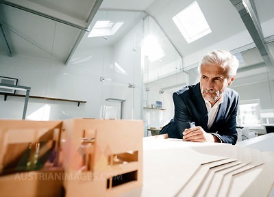 Mature businessman examining architectural model in office