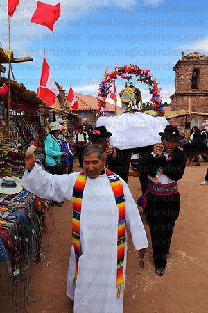 Priest blessing market stalls with alcohol at San Santiago festival , Taquile Island , Peru