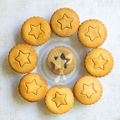 Gingerbread fruit mince pies with a star shape on the pastry lids.