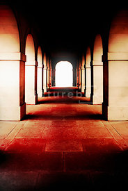 An atmospheric image of the cloisters of an old building.