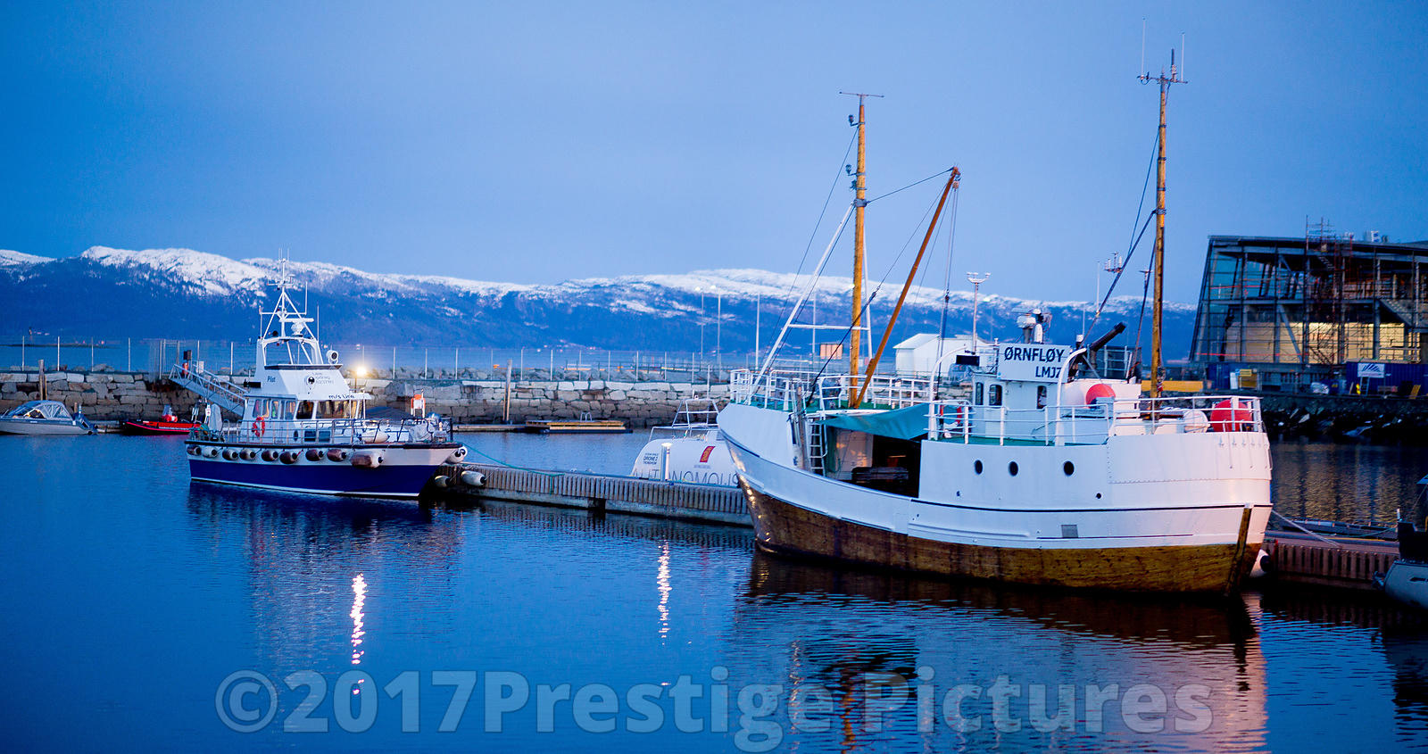 Boats in the Marina in Trondheim with snow Capped Mountains Behind - Norway royalty free stock photo library