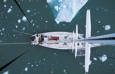 View down from top of mast to deck of sailing boat passing iceberg, arctic, Norway
