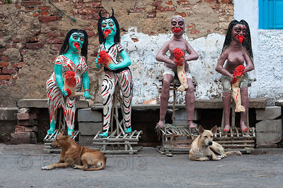 A stray dog in Kumartoli (Potter's Town) sits in front of clay idols being made for the Kali Puja festival, Kolkata, India.