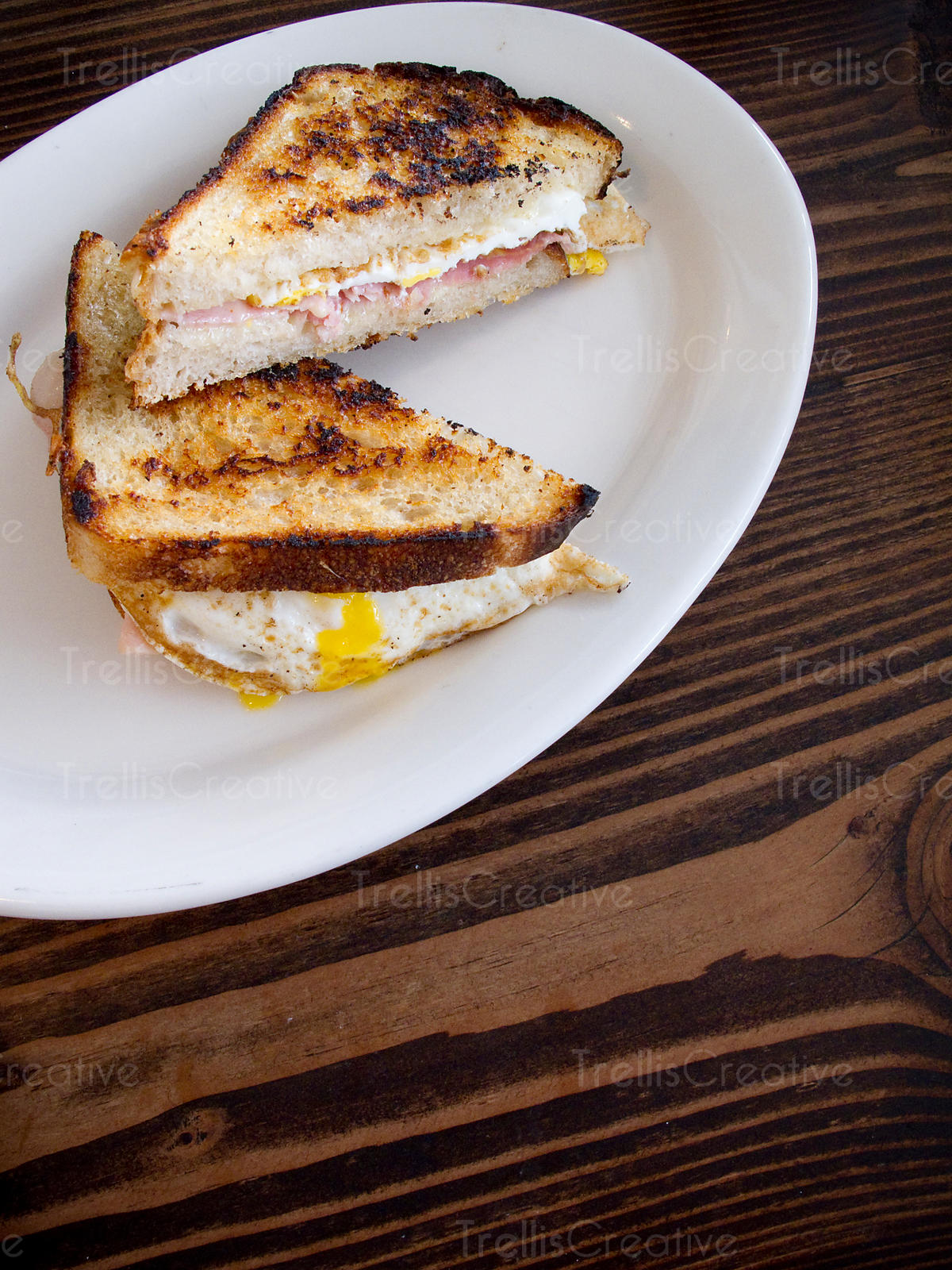 Fried egg and ham sandwich on a white oval plate