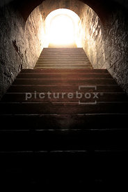 An atmospheric image of a dirty, dark underground passage, with stone steps climbing off into the daylight.