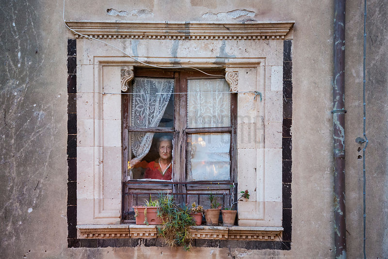 Elderly Woman Standing at the Window of her Home